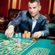 Gambler playing roulette at casino — Stock Photo #19386825