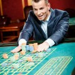 Gambler stakes playing roulette — Stock Photo #19386907