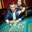 Man accompanied by woman at the casino table — Stock Photo #19387343