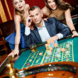 Stock Photo: Man with two girls playing roulette at the gambling house
