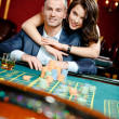 Woman embracing gambler at the roulette table — Stock Photo #19387641