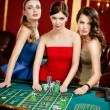 Three women place a bet playing roulette — Stok fotoğraf