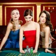 Three ladies place a bet playing roulette - ストック写真