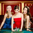 Постер, плакат: Three ladies place a bet playing roulette