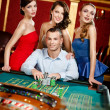 Royalty-Free Stock Photo: Man surrounded by young girls gambles roulette