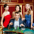 Man surrounded by ladies gambles roulette — Stock Photo