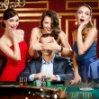Stock Photo: Girls cover the eyes of the gambler