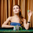 Female gambler with chip in hand at the casino — Stock Photo #19389027