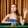 Female gambler with chip in hand at the casino — Stock Photo
