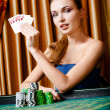 Stock Photo: Female gambler at the poker table with cards and chips