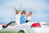 Friends stand in the automobile with hands up — Stock Photo