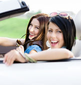 Two happy friends ride the car — Stock Photo