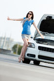 Woman thumbing a lift near the broken car — Stock Photo