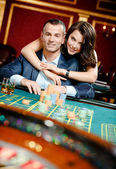 Woman embracing gambler at the roulette table — Stock Photo