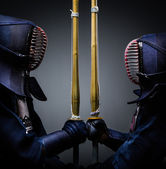 Two kendo fighters opposite each other with shinai — Stock Photo
