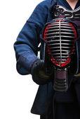 Close up of kendo helmet in hands of kendoka — Stock Photo
