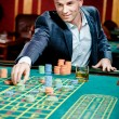 Gambler stakes playing at casino table — Stock Photo #19638273