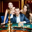 Man with two ladies playing roulette at the casino — Stock Photo