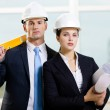Two contractors keeping level and blueprints — Stock Photo #19639779