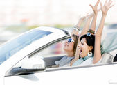 Female friends in the cabriolet with hands up — Stockfoto