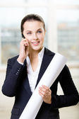 Female engineer with layout speaks on phone — Stock Photo