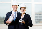 Two contractors keeping blueprints and model house — Stock Photo