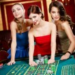 Stock Photo: Three women bet playing roulette