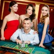 Man surrounded by girls plays roulette - Stock Photo