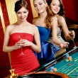 Stock Photo: Women with glasses of spirits play roulette