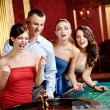 Group of young playing roulette — Stock Photo