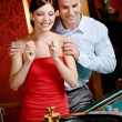 Couple playing roulette follows the game - Stock Photo