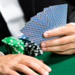 Gambler playing poker cards with chips on the table - Foto Stock