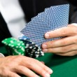 Gambler playing poker cards with chips on the table - Stock Photo