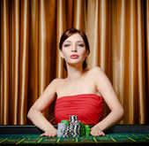 Woman stakes pile of chips playing roulette — Stock Photo