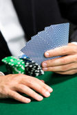 Gambler playing poker cards with chips on the table — Stock Photo