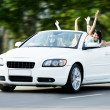Happy girls in the car with arms outstretched — Stock Photo