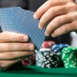 Gambler playing poker cards with chips on the poker table - Foto Stock