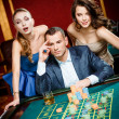 Stock Photo: Man with two girls playing roulette at the casino