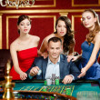 Man surrounded by pretty girls gambles roulette — Stock Photo