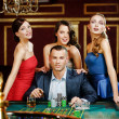 Man surrounded by pretty girls plays roulette — Stock Photo