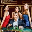 Stock Photo: Man surrounded by pretty girls plays roulette