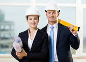Two engineers keeping level and blueprints — Stock Photo