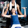 Personal coach helps woman to exercise with weights — Stock Photo