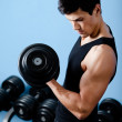 Foto Stock: Handsome muscular sportsmuses his dumbbell