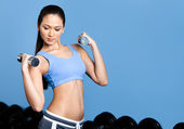 Athletic woman exercises with dumbbells — Stock Photo