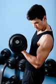 Handsome muscular sportsman uses his dumbbell — Stock Photo