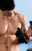 Handsome half naked man uses the dumbbell — Stock Photo