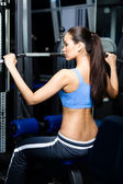 Athletic young woman works out on training gym equipment — Stock Photo