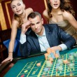 Man with two women playing roulette at the casino — Stock Photo