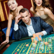 Stock Photo: Man with two women playing roulette at the casino